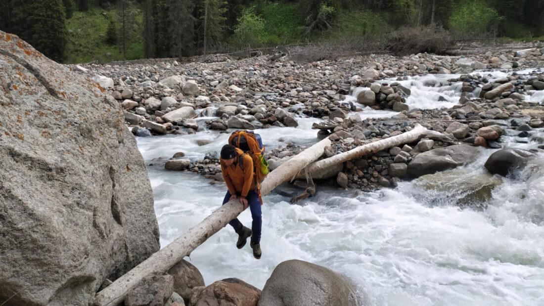 Кирилл Белоцерковский перебирается через реку по бревну